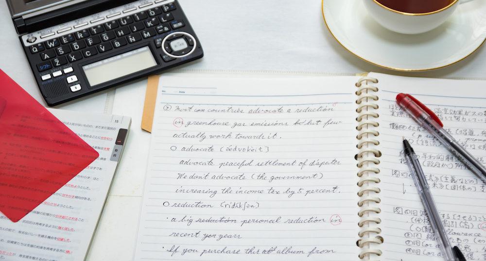 英語のノートとペンと電子辞書